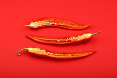 Three cut hot chili peppers on red background Stock Images