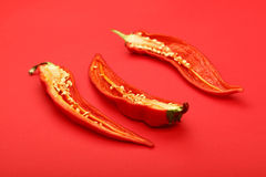 Three cut hot chili peppers on red background Stock Photos