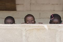 Three Cute African Children Playing Peekaboo Outdoors stock photos