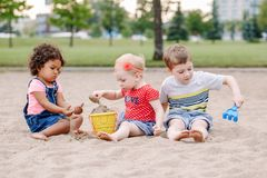 Three cute Caucasian and hispanic latin toddlers babies children sitting in sandbox playing with plastic colorful toys. Portrait of three cute Caucasian and royalty free stock photos