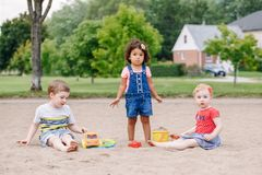 Three cute Caucasian and hispanic latin toddlers babies children sitting in sandbox playing with plastic colorful toys. Portrait of three cute Caucasian and royalty free stock photography