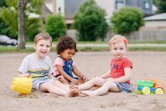 Three cute Caucasian and hispanic latin toddlers babies children sitting in sandbox playing with plastic colorful toys. Portrait of three cute Caucasian and royalty free stock photo