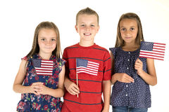 Three cute children holding American flags happy Royalty Free Stock Image