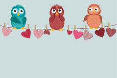 Three cute colored owlet sitting on a string. A red hearts Royalty Free Stock Photos