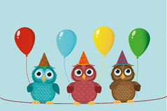Three cute colored owls sitting on a rope and holding balloons. Stock Photo