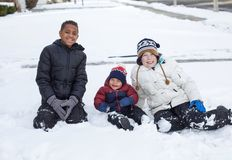Three cute diverse boys playing together in the snow outdoors stock images