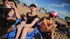 Three cute females friends joyfully sit on sandy beach sunny summer day. Three young cute women friends wearing sunglasses, hats and swimming suits joyfully sit stock footage
