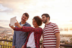 Three cute friends taking a selfie. On a tablet while on a bridge that overlooks the city and bright white clouds behind them stock photography