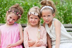 Three cute girl friends sitting together on wooden bench. Stock Photography