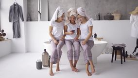 Three cute girlfriends in the same pajamas and towels on heads spending time together at home looking on the cellphone. Three happy girlfriends in the same stock video