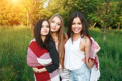 Three cute girls standing in the plaid outdoors, best friends having fun and laughing in park. Three cute girls standing in the plaid outdoors, best friends Stock Image