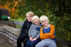 Three Cute Kids Bundled up Tractor Wagon Ride on Chilly Fall Day royalty free stock photos