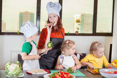 Three cute kids with mom making fruit salad Stock Image