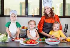 Three cute kids with mom making fruit salad Royalty Free Stock Photo