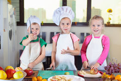 Three cute kids are preparing a fruit salad in kitchen Stock Photo