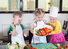 Three cute kids are preparing a salad in the kitchen Stock Photo