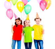 Three cute little girls with coloured balloons. Stock Photos