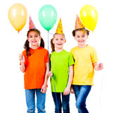 Three cute little girls with coloured balloons. Stock Images