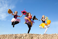 Three Cute Little Witches Jumping with Bags Royalty Free Stock Photography