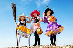 Three Cute Little Witches Standing with Bags Stock Photo