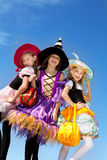 Three Cute Little Witches Standing with Bags Royalty Free Stock Image