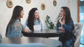 Three cute pretty girls sitting in a cafe. During this, they chat and see directly in the eye. have nice black long hair. Serious girlfriends after a long stock video footage