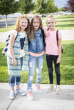 Three cute school girls heading off to school. Three cute smiling girls with backpacks on going off to school in the morning. Ready to walk to class together Stock Image