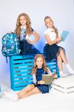 Three cute schoolgirls in a beautiful trendy school uniform with a backpack, books and notebooks with blue chair