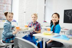 Eating at break. Three cute schoolkids sitting in classroom at break and having lunch and drinks between lessons Stock Photos