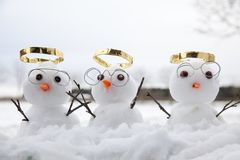 Three cute snowman angles with golden halos. And reading glasses and their wooden twig arms in the air. Snow fall on the ground at winter Royalty Free Stock Photos