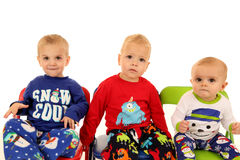 Three cute young boys sitting wearing winter pajamas Royalty Free Stock Images
