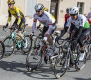 Three Cyclists - Paris-Nice 2019. Chatillon-Coligny, France - March 10, 2019: Three cyclists Andre Greipel of Arkea-Samsic Team, Lars Ytting Bak of Dimension royalty free stock images