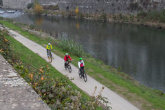Three cyclists riding along Bisenzio river embankment. Prato. Tuscany. Italy. Royalty Free Stock Images