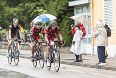 Three Cyclists Riding in the Rain. Gerardmer, France - 12.07.2014: Three cyclists, Peter Velits and Amael Moinard (BMC Team),Ben Gastauer(Ag2r-La Mondiale Team) Royalty Free Stock Photos