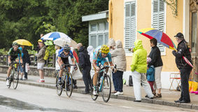 Three Cyclists Riding in the Rain Stock Photo