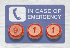 Three Wooden Pieces Depicting 911 Emergency Number. Three cylinder-shaped wooden pieces on a white wood background depicting the 911 emergency number Royalty Free Stock Photography