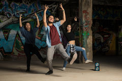 Three dancers performing together. Group of attractive Hispanic urban dancers performing a dance routine in front of a grafitti wall Stock Images