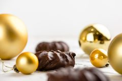 Three dark chocolate-coated zefir top view isolated on white background airy with christmas ornaments stock photography