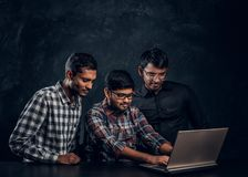 Three dark-skinned guy chatting in a laptop. Sitting eways at a desk in a studio on a black background stock images