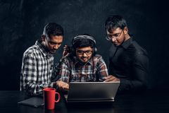 Three dark-skinned guys are chatting in the laptop wearing headphones. At the table where the cup in the studio is on a black background stock photography
