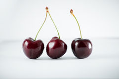 Three darkly cherries on the white table. Three darkly red cherries on the white table Stock Photo