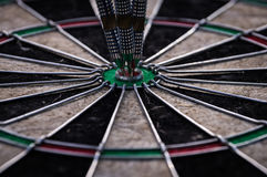 Three dart arrows hitting in the target center of dartboard Stock Images