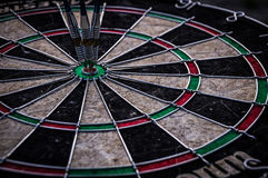 Three dart arrows hitting in the target center of dartboard. Illustrating the achievement of goals Stock Photo