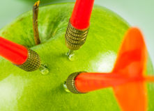 Three darts in apple Stock Images