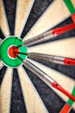 Three darts in bull`s eye Stock Photos