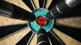 Three darts in the center of dartboard - set and achieve your aspirations and goals concept