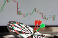 Three Darts hit target against background of chart of stock market statistics stock photo