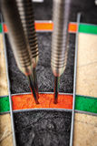 Three darts hitting perfect 180 score on dart board Stock Photography