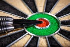Three darts lying on dartboard. Close up Stock Images