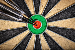 Three darts lying on dartboard. Close up Stock Photos